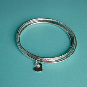 Trio of hammered bangles with heart charm